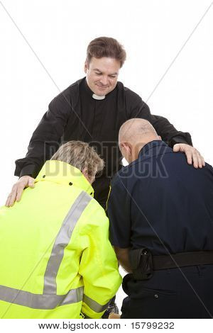 Priest or pastor gives blessing to a firefighter and a police officer who are kneeling in prayer.  White background.