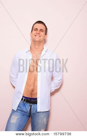portrait of a young man with unbuttoned shirt over light pink wall