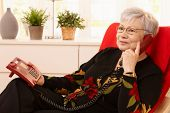 Pensioner woman using landline phone sitting in armchair in living room.?