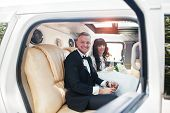 Amazing Wedding Couple Inside Elegance Limousine At Their Awesome Wedding Day. poster