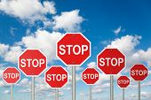 many stop signs on White, fluffy clouds in blue sky collage poster