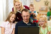 Young family in front of computer with camera having a video chat poster