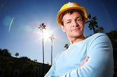 image of young adult  - Construction worker in yellow hard hat over blue sunny sky - JPG