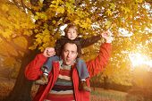 Portrait of happy father giving son piggyback ride on his shoulders in autumn park.