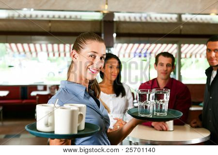 Woman as waitress in a bar or restaurant with coffee mugs; in the background are guests