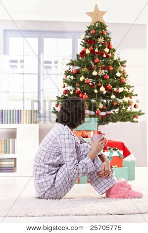 Woman in pyjama having coffee on christmas morning, looking at tree.?
