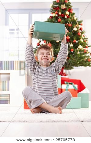 Small boy laughing, sitting on floor in morning, holding up christmas present happily.?
