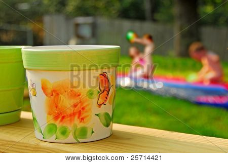 Colorful Patio Pots with Waterplaying Children in Background