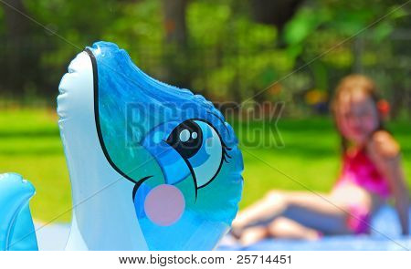 Poolside Floaty with Girl in Bathing Suit in Background