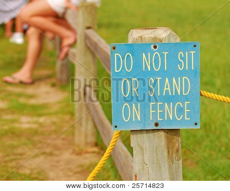 Do Not Sit on Fence Sign with Fence Sitters in Distance