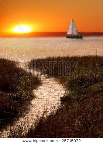 Beachside Trail at Sundown with Sailboat in distance