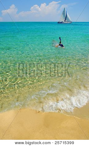 Swimmer with Fins in Ocean Heading Towards Sailboat