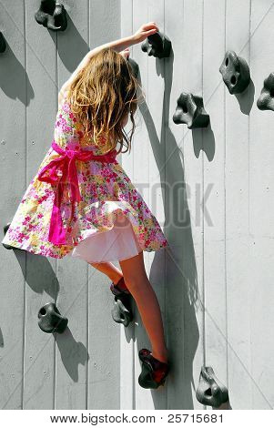 Young Tomboy Girl  in Frilly Dress Climbing Rock Wall