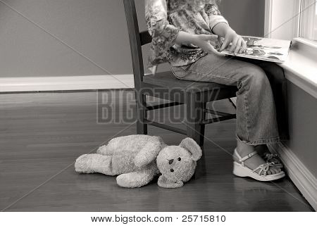 Young Girl Reading Book at Window with Stuffed Animal on Floor