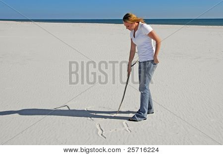 Young Woman Writing Romantic Message in Beach Sand