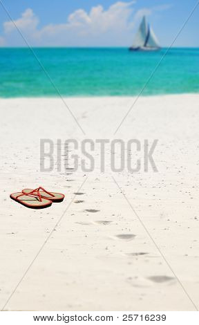 Footprints with Sandals and Sailboat in Distance