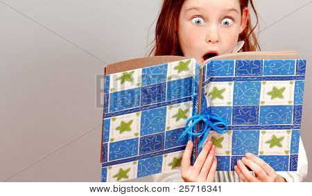 Young Girl With Huge Eyes in Exclamation Over What She's Reading
