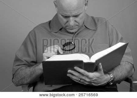 Middle Aged man using magnifier to read book