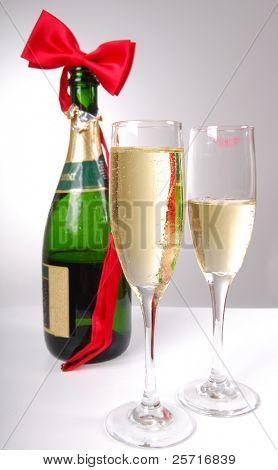 Champagne festivo y corbatín con manchas de lápiz labial en un vaso