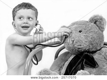 Young boy excitedly using stethoscope on toy bear
