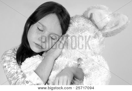 Sleepy child hugging huge stuffed rabbit