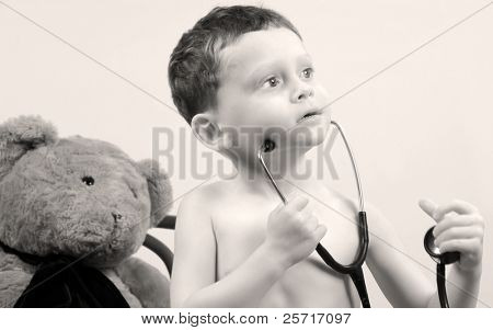 Young toddler boy with stethoscope playing doctor with bear