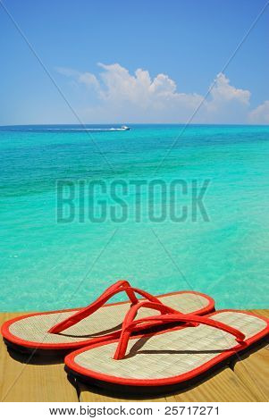 Orange flip flop sandals on dock overlooking gorgeous ocean with boat in distance