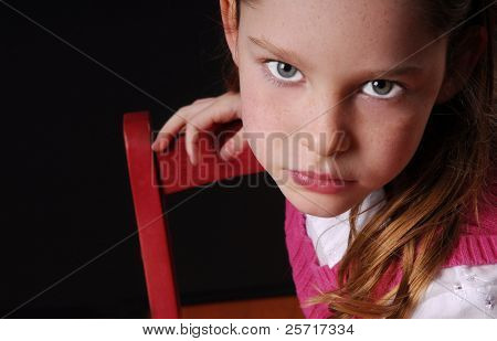 Young Girl on Red Chair Looking Serious
