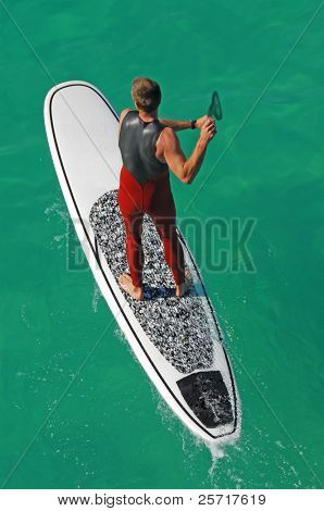 Muscular male on surfboard with paddle
