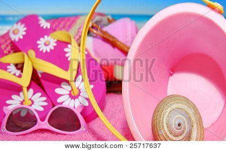 Pink sand pail, flip-flops and sunglasses on beach