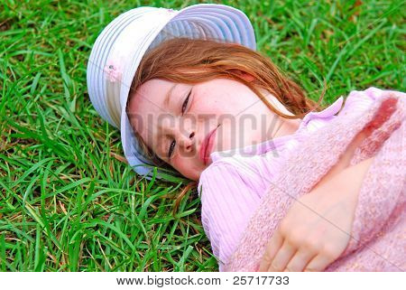 Cute Girl in Pink Laying on Green Grass