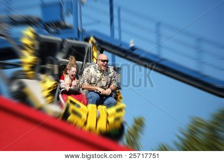 Father and daughter having fun on rollercoaster