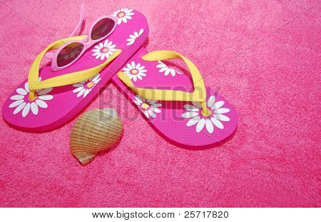 Pretty pink flip flop sandals, sunglasses, and seashell on pink beach towel