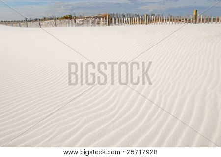 Beautiful rippled sand dune leading up to fence in afternoon sun