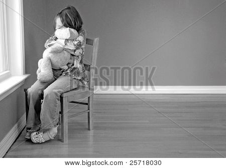 Young girl hugging stuffed animal looking out of window