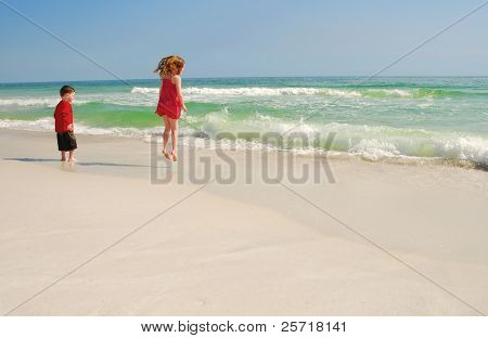 Young boy and girl playing happily at beach