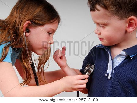 Cute young girl listening to cute young boy's heart
