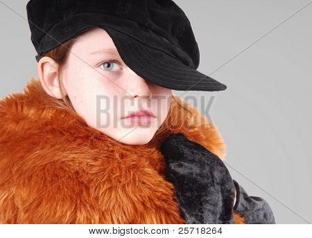 Pretty freckle faced girl wearing black cap, gloves, and fancy coat
