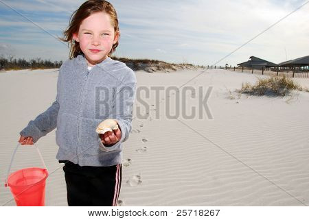 Young girl with pail and shell on pretty rippled beach