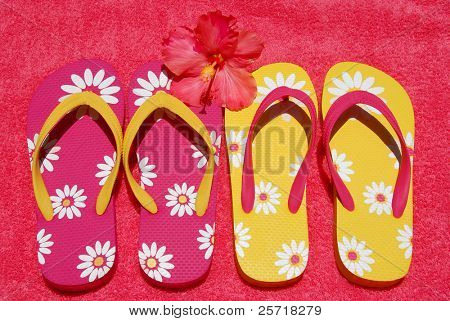 Pretty colorful flipflops on beach towel with hibiscus blossom