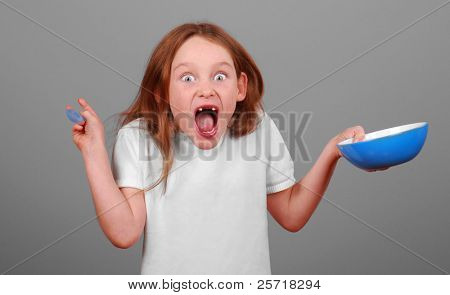 Toothless freckle faced girl making excited face holding bowl and spoon