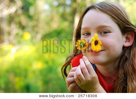 Cute girl smelling fresh picked daisies outside