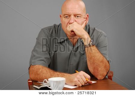 Man at desk with calculator and note paper looking serious or thoughtful