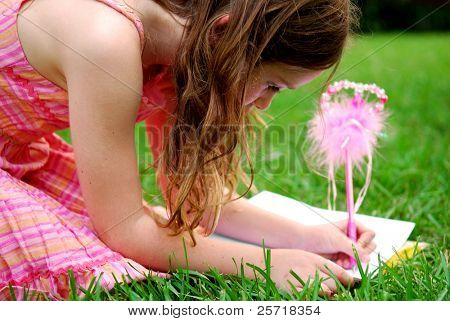 Cute young girl using fancy pen to write in journal outside