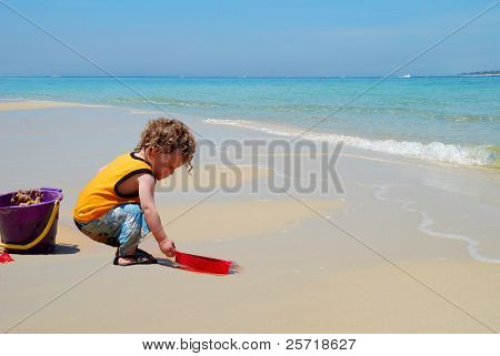 Curly headed toddler boy playing with sand on beach