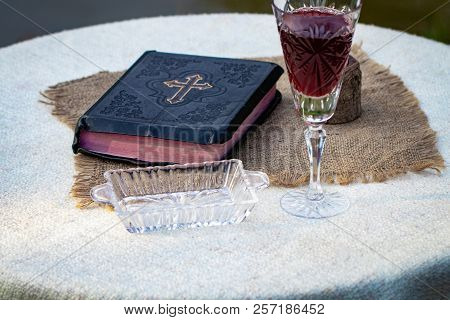 Taking Communion  Cup Of Glass With Red Wine, Bread And Holy Bible On  Wooden Table Close-up poster