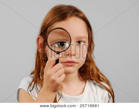 Niña mirando a través de la lupa con enormes ojos