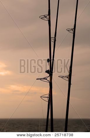 Silhouette of fishing poles at ocean at dusk