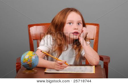 Pretty young girl at desk working on school assignment