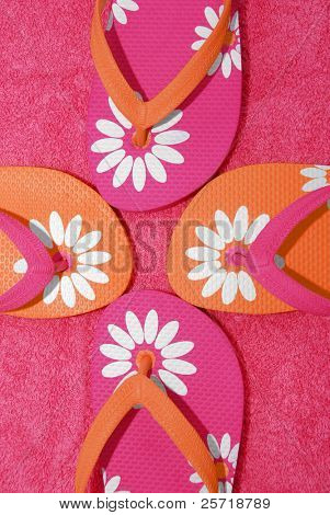 Pretty array of pink and orange flipflop sandals on beach towel